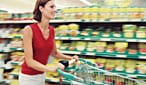 A woman pushes a shopping trolley around a supermarket.