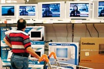 Man looking at televisions whilst in a supermarket