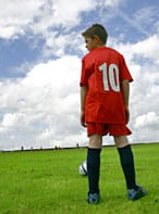 Boy in red kit on football pitch