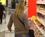 A woman in a supermarket reading a food label