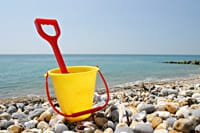 A bucket and spade on a beach