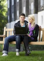 Couple surfing internet on a park bench