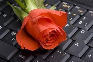 Internet dating - red rose on laptop keyboard