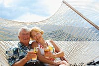 A retired couple on a rope hammock