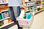 A man carrying a shopping basket in a supermarket