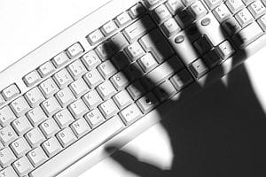 Cybercrime - hand shadow over computer keyboard