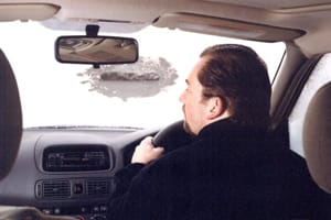 Man driving with frozen windscreen