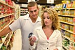A couple reading a food label in a supermarket