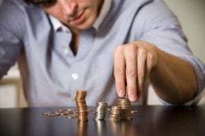 Man counting coins in piles