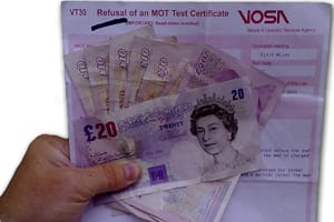 Hand holding MoT test certificate and cash