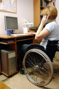 Woman in wheelchair using computer and phone