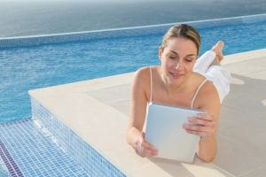 Woman using tablet by pool