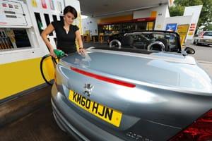 Woman filling car up at petrol station