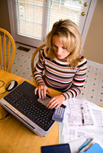 Woman using a computer to repay debts