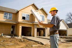 House builder in front of part-built new home