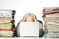 Work piling up (man with laptop)