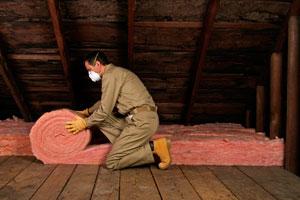 A man installing loft insulation