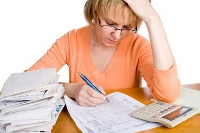 Lady looking at energy bills with calculator