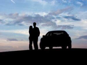 Couple stood next to a car looking into the distance at dusk