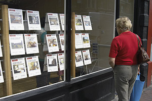 A woman looking in an estate agency window