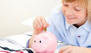 Boy inserting coins into a piggy bank
