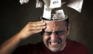 Sheets of paper with 'bills' written on them coming out of the top of a man's head
