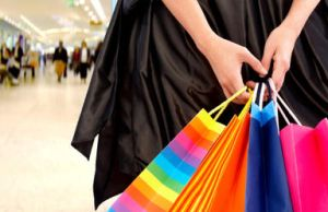 Close up of brightly coloured shopping bags clutched by a woman's hand