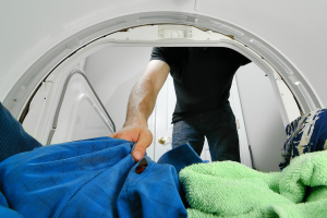 Man reaching into tumble dryer