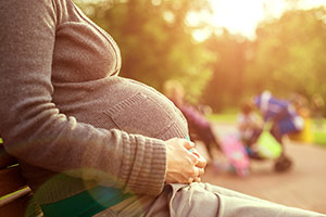 Pregnant woman sitting on park bench