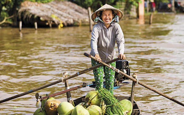 Vietnam - a fruit seller rowing on the Mekong Delta