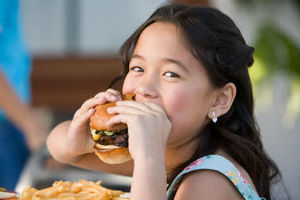 Young girl enjoys her burger at a restaurant