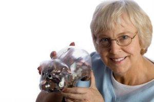 elderly woman smiling with piggy bank