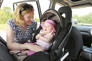 Woman-strapping-baby-into-car-seat
