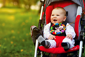 Happy baby in red pushchair on grass