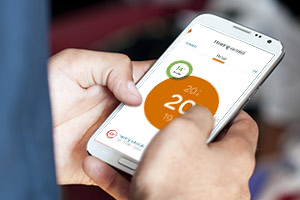 Someone using the Hive smart heating control app on the mobile phone