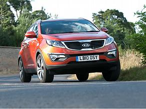 Kia Sportage orange driving f3q