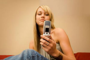 young blonde woman looking at her mobile phone screen