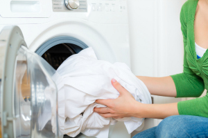 A woman putting sheets in a tumble dryer