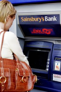 woman withdraws money from sainsbury's bank cashpoint