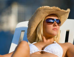 Blonde woman sunbathing in hat and sunglasses