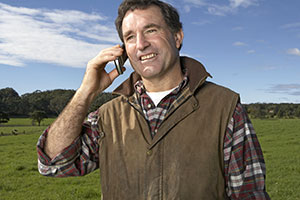 Man in rural setting uses mobile phone