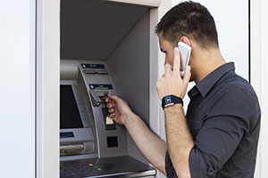 Man on phone whilst using cash machine