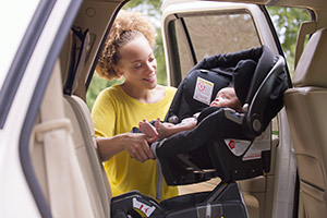 Parent fitting child car seat into car