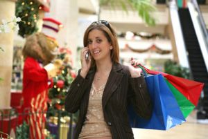 Woman in a shop with shopping bags draped over her shoulder at Christmas