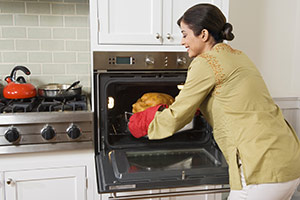 Woman taking food from built-in oven