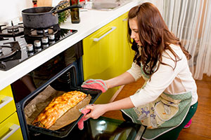 Woman taking food from oven