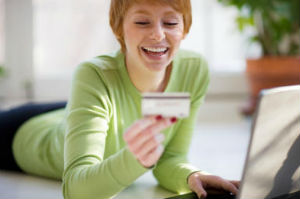 Pleased ginger woman looking pleased with her credit card and laptop