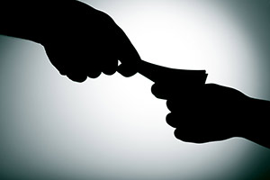 Silhouette of money changing hands