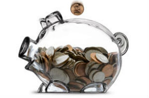 coin dropping into clear piggy bank