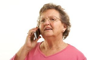 Concerned elderly woman with glasses using a mobile phone